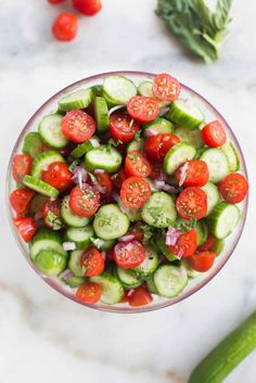 A clear bowl filled with halved grape tomatoes and english cucumbers cut into thin slices.