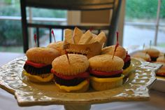 """Hamburger cupcakes!  Part of a chocolate cupcake between two halves of white cupcakes, with yellow and red frosting as condiments.  And served with sugar cookie """"fries"""".  Perfect for a teenage boy's party!"""