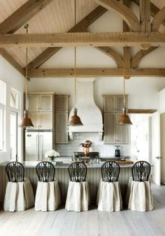 Great kitchen in this timber frame home.  The contrast of white with the natural wood elements (and pendant lights) is great.