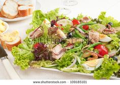 Salade Nicoise is made with  canned tuna, anchovies, hard boiled eggs, tomatoes, cucumber, olives, onions, lettuce, potatoes and green beans, with a dressing flavoured with fresh garlic and mustard.