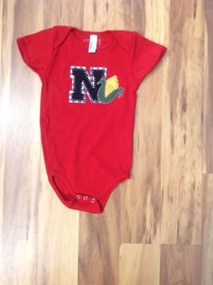 Short Sleeved Red Onesie with Black N and Black/White Checkered Backing and Ear of Corn