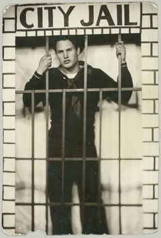 "Arcade photo of sailor behind bars of ""City Jail,"" but something tells me this guy might be a real bad boy."