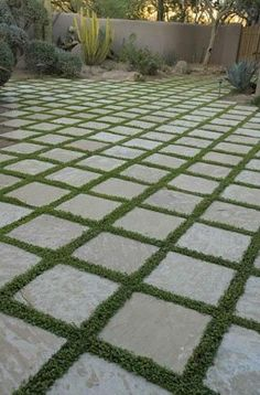 """We like the way A Tile Guide describes the paving in this photo as having """"grass for grout"""". Twelve-by-twelve stone tiles are laid out in a grid, with grass in the joints instead of grout"""