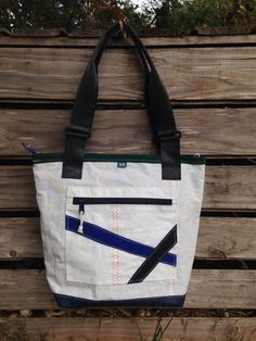 This is a fun colourful tote made from an upcycled sail with accents of blue and green Sunbrella. There is a zipper closure across the top, and a zippered pocket to keep your valuables secure. Recycled sails make great bags; light weight, durable and environmentally responsible. Dimensions: The length is 15.5 across the top, 6 wide, 11.5 across the bottom and 13.5 high.  The shoulder strap measures 26.5 from one side to the other.  Each bag is unique and may have slight imperfections or…