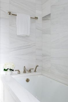 A polished nickel towel bar is fixed to mixed size white marble wall tiles above. A polished nickel towel bar is fixed to mixed size white marble wall tiles above a drop-in bathtub fitted with a polished nickel tub filler mounted to a marble deck. Marble Bathtub, Drop In Bathtub, White Marble Bathrooms, Marble Wall, Wall Tiles, Mold In Bathroom, Small Space Bathroom, Bathroom Spa, Master Bathroom