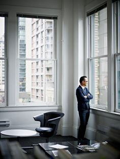 Foto de stock : Smiling businessman looking out office window