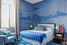 A custom-made tapestry of the Bay of Naples dominates the master suite, where the bed, with a headboard and bed skirt fashioned from fabric found at Istanbul's Grand Bazaar, is dressed with an ikat pillow by the Rug Company, a coverlet made from vintage toile de Jouy, and a cashmere throw by Loro Piana; Allegra Hicks prints were used for the curtains and the armchair and its pillow.