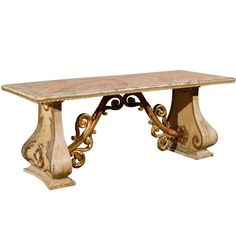 This Italian 19th century console table has an incredible Baroque presence. From its richly decorated carved legs emerges its gilded wood stretcher whose volutes come and meet at the center. Its faux marble top, wrapped in a thin molding, crowns this beautiful Italian console table that will be a show stopper and will make be a wonderful addition to your home.