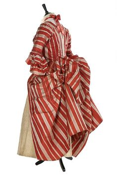 Siede view, robe à la polonaise, France, 1770s. Ivory and cinnamon striped silk satin, English back; with ivory satin stomacher covered with pinked ribbon rosettes and a finely quilted ivory satin petticoat with overall lattice design and flowerheads within triangles to the hem.