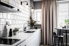 Köket med bänkskiva i marmor, vita stommar och vitt 15x15 cm kakel med svart fog.
