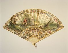 """Fan, France, 1760-1770, """"Chickenskin"""" vellum leaf, painted gouache. 20 stitcks, 2 guards: ivory, carved pierced and painted.  Leaf: Face: Chickenskin, painted in gouache with a shepherd and shepherdess in a woodland clearing, shepherd playing the musette. Three attendant sheep and a large classical urn. Multi-coloured and gold border of swags, flowers and scrolls and edging of gold paper. Sticks: Ivory, carved, pierced and painted in polychrome and gilding. Guards: Carved and pierced."""