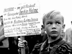 This image depicts a sadly common event in the aftermath of war: Hans Heime holds a sign asking for information from returning soldiers if they have any information about his father, Joachim. (1946)