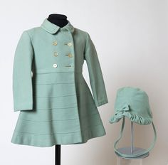 This matching coat and bonnet set was made by Minimode in the early 1960s. It was worn by a girl called Karen when she was about three years old. Minimode produced good quality and stylish clothing for children from around the late 1950s. This set was bought by Karen's mother in a childrenswear shop in Harrow, England in 1961.