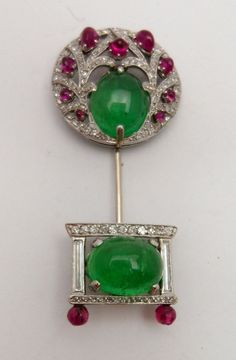 A platinum set jabot pin by Koch. Stylised tree with cabochon emeralds and rubies and diamond.