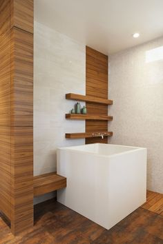 Stunning White Scheme Granite Materials Japanese Soaking Tubs for Bathroom Furniture on the Brown Solid Wood Flooring with Modern Metal Chrome Faucet adhere on the Three Levels Brown Wood Wall Shelf