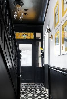 Crisp black and white paint, glam gold light fixtures, and a graphic patterned floor transform this entry hall from bland to beautiful!