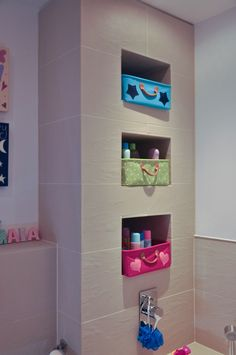 Niche storage areas with bright boxes adding colour and fun to this family bathroom.  This family bathroom was designed and specified by Cat Lock our Creative Director.