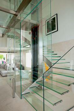 """O vidro impera na escada projetada pela arquiteta Fernanda Marques para o apartamento em S. Paulo, Brasil. A ideia é valorizar os espaços sociais e integrá-los. A escada e a caixa do elevador, de vidro, conectam o living ao home theater e ao exterior. A passarela no andar de cima é sustentada por estrutura de aço inox, e os degraus e o guarda-corpo são fixados por """"botões"""" de aço inox de um lado e, na faixa em """"L"""", do outro. O conjunto confere leveza visual à residência.  Fotografia…"""