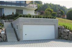 Diese Garage ist Teil des Gartens und hält sich in der Gestaltung entsprechend zurück. Frisba