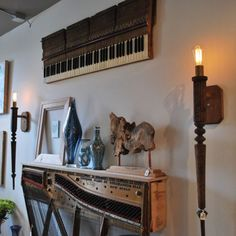 Love this! Repurposing a piano--the legs as sconces, keyboard as wall-art, sound board as side table.  If unplayable, great way to appreciate  a beautiful instrument.