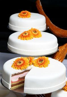 Schlichte Hochzeitstorte in Weiß mit orangenen Gerbera-Blüten als ...