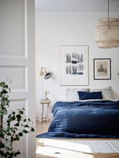 Relaxed style with blue covers, stool bedside table and art