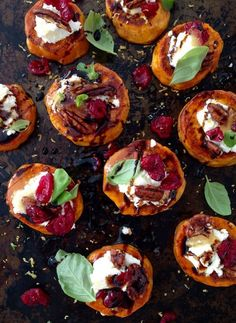 A Black Tray of Sweet Potato Rounds Appetizers Topped with Goat Cheese, Candied Walnuts, Cranberries & Balsamic Glaze