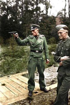 Panzer Heer officer practiced his aim with his trusty Luger P-08 handgun alongside one of his crewmen.