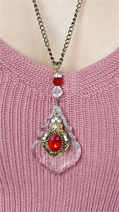 Chandelier glass baroque crystal embellished red and gold beaded pendant necklace.    The faceted clear upcycled crystal hangs from a 24 inch bronze chain and has an ornate gold teardrop framed red acrylic bead that hangs freely ontop of it. There are tiny clear rhinestoneson it.    The crystal is attached to the necklace by a thin silver jump ring which leads to clear and red crystalsand a rhinestone spacer bead charm.    The crystal measures 55 x 38 mm at widest points.   The total drop is…