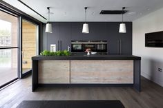Roundhouse Urbo and Metro matt lacquer bespoke kitchen in Farrow & Ball Railings and horizontal grain Driftwood veneer with worktop in Nero Assoluto Linen Finish with honed edges.