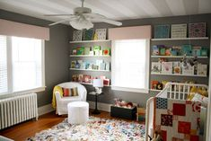 Where do I start so many things about this nursery are adorable!  the book shelves/picture rail is a great idea and the rug could be re-created by putting together mult urban outfitters rag rugs together since they are fringy you wouldn't see the seams.  Also the grey color really works great with all the pops of color from the books and bedding