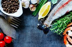 #Raw rainbow trout  Seafood background with raw rainbow trout shrimps and ingredients on black slate stone board preparation top view copy space. Healthy food diet or cooking concept