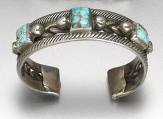 A Navajo bracelet  On twisted wire and thick crosshatched side bands, aligning a trio of turquoise stones accented by pairs of silver drops.  width 2 7/8in