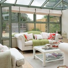 After conservatory ideas? Take a look at this lovely green conservatory furnished with cream sofas and bright cushions and throws for inspiration. Find more design ideas at housetohome.co.uk