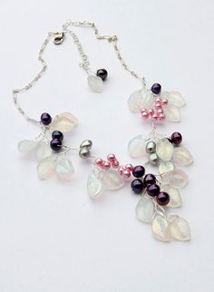This sweet pink purple flower beaded necklace features freshwater pearls and Czech Glass leaves. White leaves dangle from a twisted wire