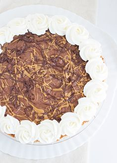 Dark Chocolate Peanut Butter Pie - rich chocolate and peanut butter cheesecake mousse topped with whipped cream swirls and peanut butter swirls. It's a must try!