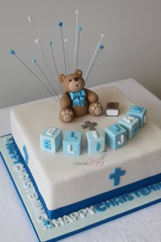 Christening cake for baby boy, complete with fondant teddy bear, letter blocks, bible and cross.  All edible, except for stars on wire. www.cakeme.com.au