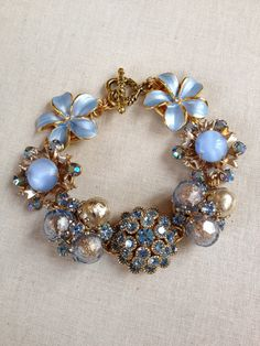 This bracelet is made with seven pretty repurposed vintage earrings and rhinestone buttons in shades of light blue. Each of the seven vintage
