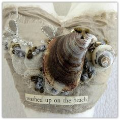 washed up on the beach - a textile art heart with shells and silver embroidered leaves