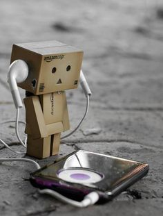 Danbo (or Danboard) is a cute cardboard robot that partly represents the human being. Small, cute robot gives an opportunity to recreate… Danbo, Iphone Wallpaper Music, Cardboard Robot, Box Robot, Amazon Box, Whatsapp Dp Images, Cute Box, Little Boxes, Listening To Music