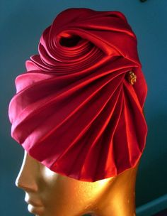 """Lina Stein: Let the centrifugal powers draw you into the Whirls and depths of this creation. Simply follow the luscious red satin pleats around as they become closer and tighter until they descend into the """"ever faster turning stream"""" of this hat. You may ask - Where will this lead you? I can only say into the Whirl pools of desire! Constructed on a foundation of pleated Bias-Sinamay, the heavy red Bias-cut satin sits tightly, hugging the movements of the pleats underneath. The vintage-st..."""