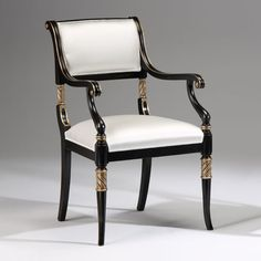 Regency style carved beechwood armchair in antiqued black finish with antiqued silverleaf trim and off-white upholstery; Made in Italy.