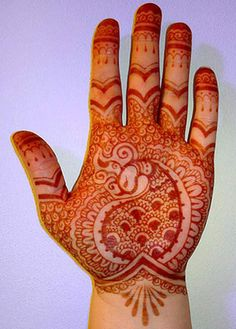 This beautiful design features red mehndi. The design features peacock motif in the middle of the palm.
