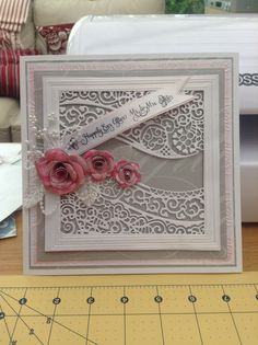 Spellbinders grand squares, tattered lace free die, creative expressions Sue Wilson classic rose die, justrite sentiments stamps, K & Co papers, embossalicious rose embossing folder, pearl sprays from country baskets and pearl string from creative expressions.