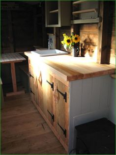 Tiny house kitchen - Barn door hinges on the natural/white cabinets, sunflowers, green semi-opaque stain on the upper cabinets