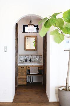 アーチの下がり壁の奥に設けた洗面台。 シャンデリアやランタンタイルがかわいいナチュラルなサニタリー空間にしあがりました。