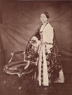 Queen Victoria.   Creator:After Roger Fenton (1819-69) (photographer)  Creation Date:after an original of 8 Feb 1854  Materials:Printed in carbon by Mullins in 1889  Dimensions:21.1 x 15.9 cm  RCIN  2906507  Provenance:Commissioned by Queen Victoria in 1854  Description:Photograph showing full length portrait of Queen Victoria taken at Windsor Castle. She has her hands placed on the back of a chair and wears a cloak over a her dress.