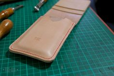 I use a Belkin plastic iPhone case to stretch the leather into shape. I find that it works better than using the phone because I dont have to worry about ruining it with moisture and having it slightly bigger than the phone also makes the shape more ideal (the phone will slide in and out a bit easier). You could also use the phone itself or just stretch the leather into shape with your hands.