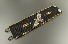 This Native American inspired loom woven bracelet is made using Miyuki Delica seed beads. Thirteen vibrant colors embody this powerful eagle. He is flanked by single feathers against a matte black background. Opaque black beads are thrown into the background for a slight sparkle. The edge is lined with a Broken Post and Rail fringe in the color of buckskin. Two pewter buttons are woven into the body of the cuff as clasps. * Material: Miyuki Delica seed beads (size 11), Nymo D Thread, 2…