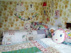 Sweet Old Fashioned Girls Room.  Iron Beds, Patchwork Quilts, Vintage Wallpaper, Doll Face Pillows